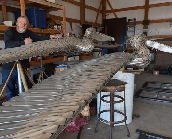 Sculptor stands with two metal pelican sculptures in workshop