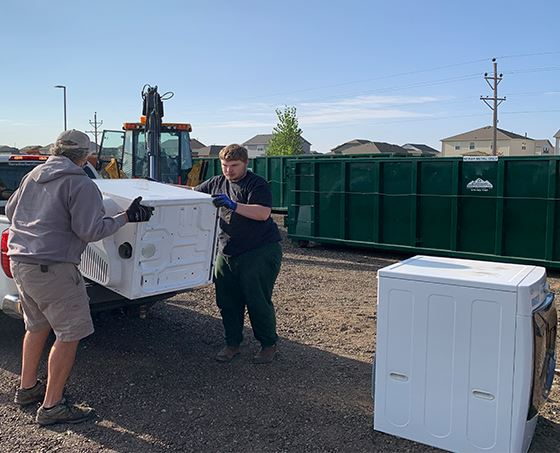 Two Windsor residents unloading a washing machine at the 2020 fall clean up event.